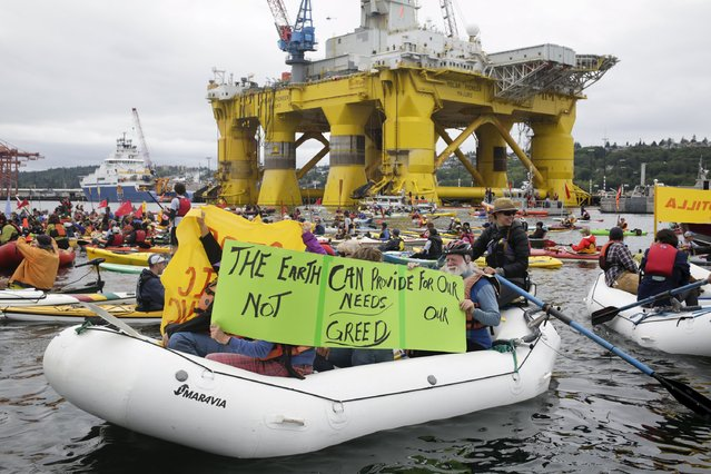 Activists protest the Shell Oil Company's drilling rig Polar Pioneer which is parked at Terminal 5 at the Port of Seattle, Washington May 16, 2015. Hundreds of activists in kayaks and small boats fanned out on a Seattle bay on Saturday to protest plans by Royal Dutch Shell to resume oil exploration in the Arctic and keep two of its drilling rigs stored in the city's port. (Photo by Jason Redmond/Reuters)