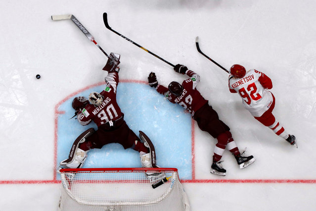Latvia's Elvis Merzlikins and Teodors Blugers and Russia's Yevgeny Kuznetsov in action during the Ice Hockey World Championships group B match between Latvia and Russia at the Ondrej Nepela Arena in Bratislava, Slovakia, Saturday, May 18, 2019. (Photo by Vasily Fedosenko/Reuters)