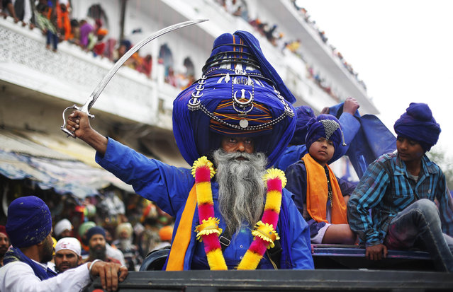 """Sikh warrior Major Singh, wearing a 425 meters long turban, brandishes a sword as he participates in a religious procession during the annual fair of """"Hola Mohalla""""  in Anandpur Sahib, in the northern Indian state of Punjab, Monday, March 17, 2014. (Photo by Altaf Qadri/AP Photo)"""