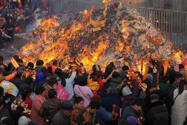 This photo taken on February 27, 2017 shows pilgrims throwing items into a bonfire during a temple fair at the Tai Hao Tomb Temple in Huaiyang County in Zhoukou in China's central Henan province. Visitors and pilgrims from home and abroad gathered at the temple to pay homage to Tai Hao, one of the ancestors of the nation according to Chinese mythology. (Photo by AFP Photo/Stringer)