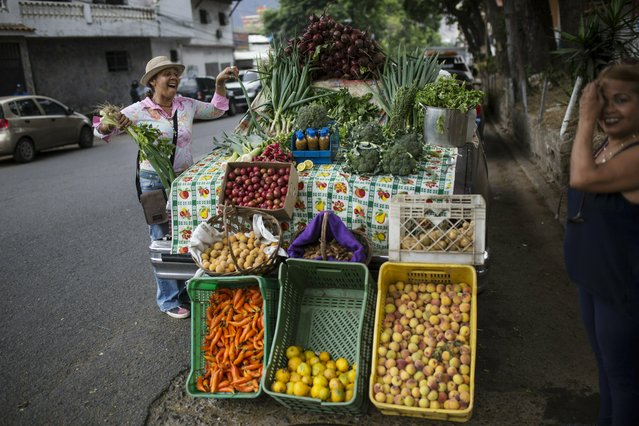 Nancy Espinoza, 55, who uses an old car as her stand, sells vegetables to a customer in Caracas, Venezuela, Friday, May 3, 2019. (Photo by Rodrigo Abd/AP Photo)