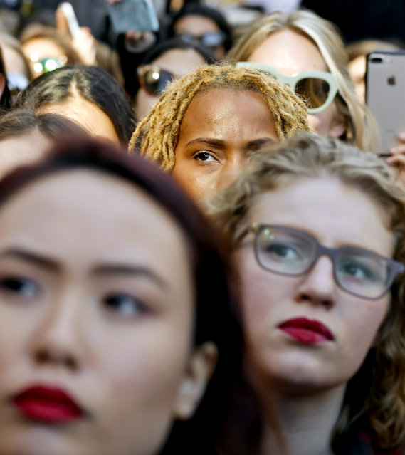 Participants listen to remarks from a speaker at the International Women's Day rally in the shadow of New York's Trump Tower, Wednesday March 8, 2017, in New York.  The protest was part of a nationwide event called A Day Without a Woman. Many of the participants had taken a day off from work to show the impact women have on the American economy. (Photo by Bebeto Matthews/AP Photo)