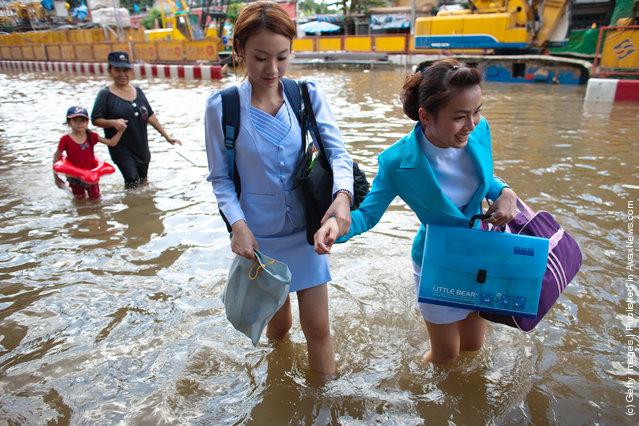 Women walk through a flooded street in Bangkok, Thailand