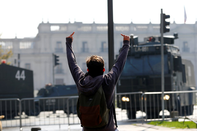A student protester gestures in front of riot police vehicles during a demonstration to demand changes in the education system in Santiago, Chile, April 21, 2016. (Photo by Ivan Alvarado/Reuters)