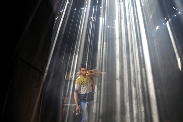 A Palestinian worker carries clay pots as the sun rays penetrate through the ceiling of a pottery workshop in Gaza City on June 11, 2019. (Photo by Mohammed Salem /Reuters)