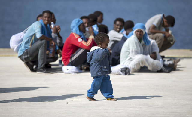 A children walks as migrants rest after disembarking from the expedition vessel Phoenix in the Sicilian harbour of Augusta, Italy June 17, 2015. REUTERS/Antonio Parrinello      TPX IMAGES OF THE DAY