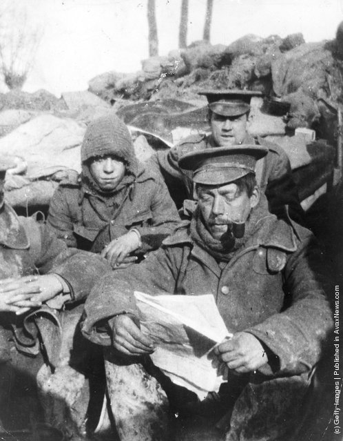 1915: Infantrymen sitting in a trench reading and smoking during the early days of trench warfare in the First World War