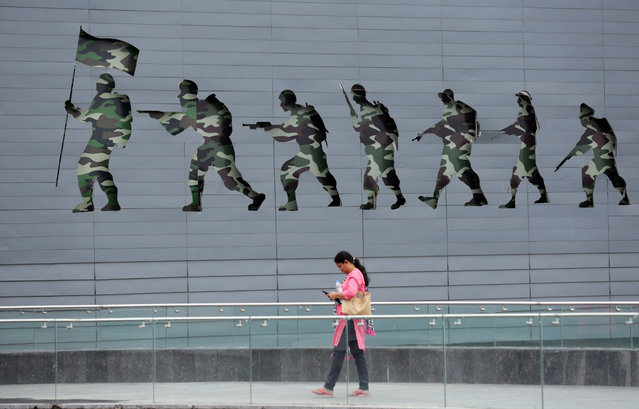 """A visitor looks at her phone as she walks after an event to pay tributes to the Kargil war martyrs at the Punjab State War Heroes' Memorial and Museum on the occasion of """"Kargil Vijay Divas"""" or """"Kargil Victory Day"""" in Amritsar, India, 26 July 2019. According to reports, more than 500 Indian soldiers were killed in the Kargil war between India and Pakistan that lasted for two months in 1999. (Photo by Raminder Pal Singh/EPA/EFE)"""