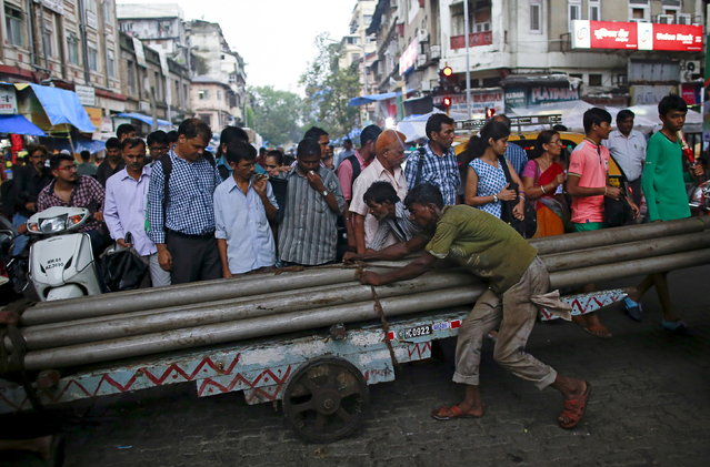 Porters transport metal pipes on a wooden handcart as people wait to cross a street in Mumbai, June 24, 2015. (Photo by Danish Siddiqui/Reuters)