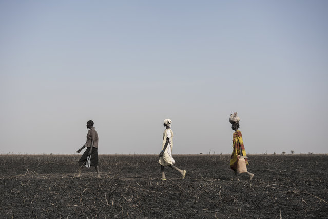 In this photo taken Saturday, March 11, 2017, women walk across parched and burned former farmland on the outskirts of Aweil, in South Sudan. (Photo by Mackenzie Knowles-Coursin/UNICEF via AP Photo)