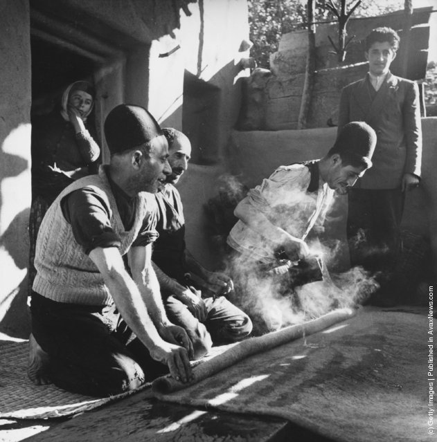 1950:  Iranian peasants making rugs by kneading pieces of wool together after steaming them under pressure
