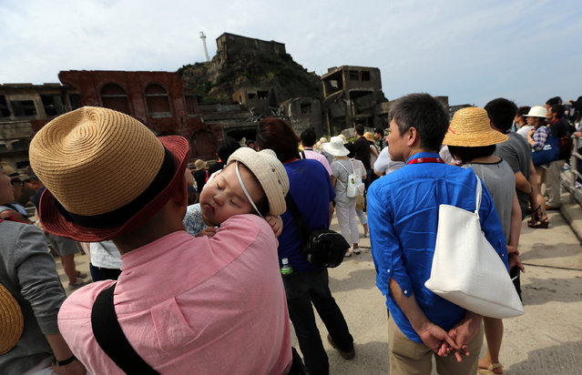 "In this June 29, 2015 photo, tourists visit at Hashima Island, commonly known as Gunkanjima, which means ""Battleship Island"", off Nagasaki, Nagasaki Prefecture, southern Japan. (Photo by Eugene Hoshiko/AP Photo)"