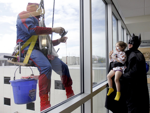Rosie Highley, 3, of Pasco, gets a lift on Tuesday, April 22, 2014, from Jason Klovansky, dressed as Batman, to wave at Richard Shirley, dressed as Spiderman, while he washes windows at Kadlec Regional Medical Center in Richland, Wash. Klovansky and Shirley, and two other employees of Sparkling Clean Windows in Kennewick, dressed as superheroes to entertain patients and families at the Don and Lori Watts Pediatric Center while doing the windows. (Photo by Sarah Gordon/AP Photo/The Tri-City Herald)