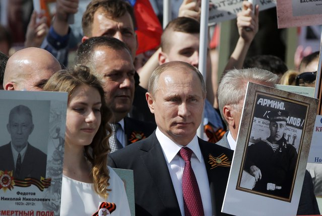 Russia's President Vladimir Putin holds a portrait of his father Vladimir Spiridonovich Putin, who fought in World War II, during the Immortal Regiment march in Moscow, May 9, 2016, marking the 71st anniversary of the victory over Nazi Germany in WWII. (Photo by Mikhail Metzel/TASS via Newscom)