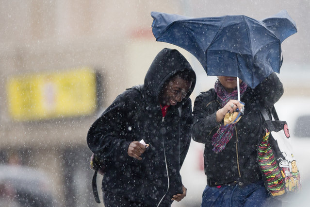 Pedestrians walk with little protection from their collapsed umbrella during a rainstorm, Wednesday, April 30, 2014, in Philadelphia. The area can expect widespread showers with possible thunderstorms with a flood watch in effect through Thursday morning. (Photo by AP Photo)