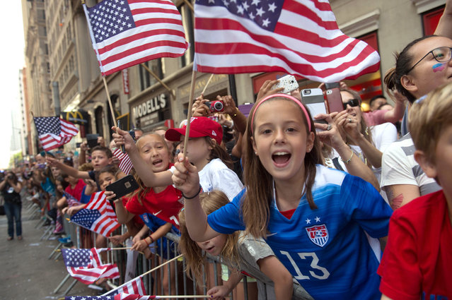 Fans cheer as the U.S. Women's World Cup soccer champions parade through Broadway to City Hall, Friday, July 10, 2015, in New York. (Photo by Bryan R. Smith/AP Photo)