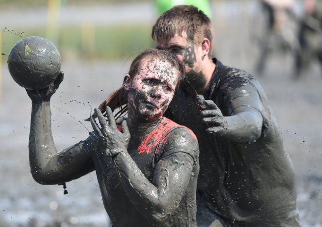 """Players fight for the ball during a handball match at the so called """"Wattoluempiade"""" (Mud Olympics) in Brunsbuettel at the North Sea, July 11, 2015. (Photo by Fabian Bimmer/Reuters)"""