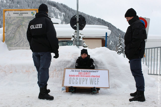 Swiss riot police men frame an Occupy protester checking personal datas in front of the main gate to Davos congress center