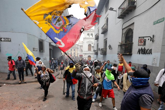 A protester waves a desecrated national flag during a march against President Lenin Moreno and his economic policies during a nationwide strike in Quito, Ecuador, Wednesday, October 9, 2019. Ecuador's military has warned people who plan to participate in a national strike over fuel price hikes to avoid acts of violence. The military says it will enforce the law during the planned strike Wednesday, following days of unrest that led Moreno to move government operations from Quito to the port of Guayaquil. (Photo by Carlos Noriega/AP Photo)