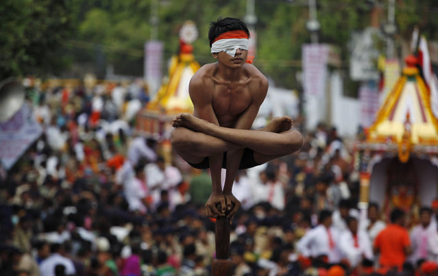 An Indian boy practices Mallakhamb, a traditional Indian gymnastic sport on a vertical wooden pole during the annual Rath Yatra, or Chariot procession, in Ahmadabad, India, Saturday, July 18, 2015. (Photo by Ajit Solanki/AP Photo)
