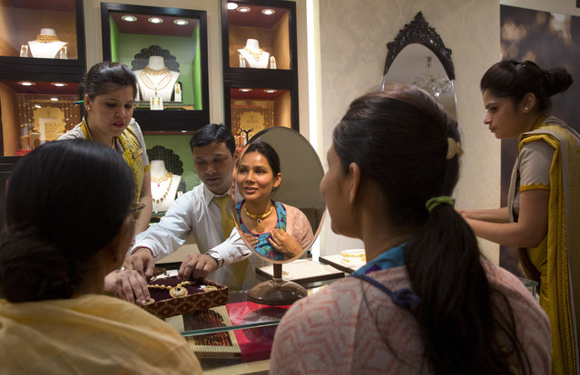 """An Indian girl checks out a gold necklace at a jewelry on the eve of """"Akshay Tritiya"""" festival in New Delhi, India, Thursday, April 27, 2017. Friday marks the Hindu festival """"Akshay Tritiya"""", considered auspicious for buying gold among other things. (Photo by Manish Swarup/AP Photo)"""