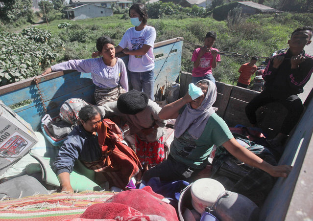 Villagers board a truck as they are transported from their homes too close to the danger zone following the eruption of Mount Sinabung in Gamber village, North Sumatra, Indonesia, Sunday, May 22, 2016. (Photo by Binsar Bakkara/AP Photo)