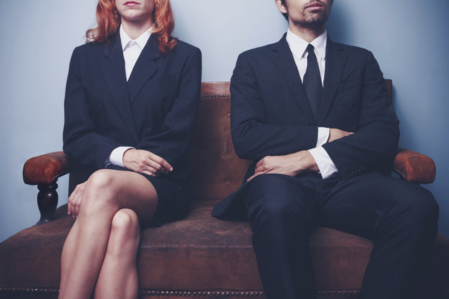 Two sharply dressed business people are waiting on a sofa with a serious expression on their faces. Maybe they're waiting to enter a job interview, or maybe they're a couple waitng to see a divorce lawyer. (Photo by Lofilolo/Getty Images/iStockphoto)
