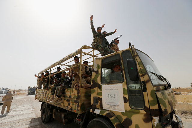 Iraqi security forces ride in a military vehicle near Falluja, Iraq, May 24, 2016. (Photo by Thaier Al-Sudani/Reuters)