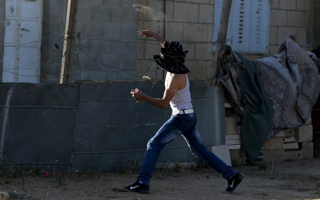 A Palestinian protester throws a stone at Israeli troops following a protest against Jewish settlements in the West Bank village of Silwad, near Ramallah July 24, 2015. (Photo by Mohamad Torokman/Reuters)