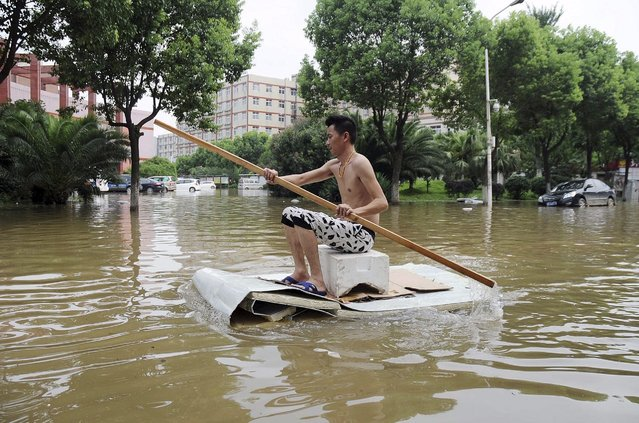 A man paddles a makeshift boat along a flooded street after heavy rainfall hit Wuhan, Hubei province, China, July 24, 2015. (Photo by Reuters/Stringer)