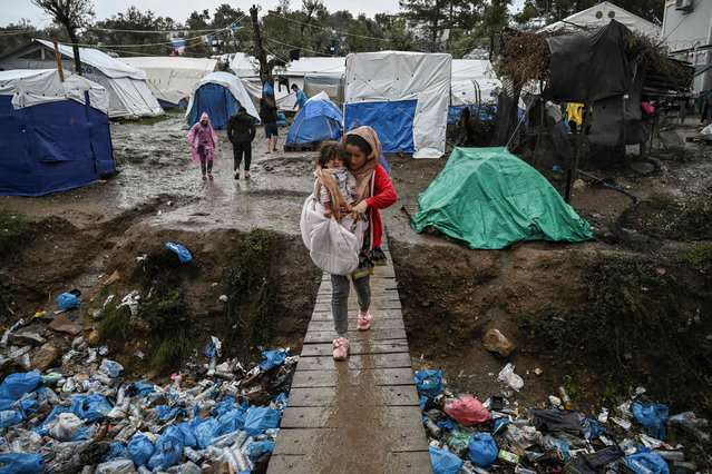 A womancarries her child as she crosses a wooden bridge in the refugee camp of Moria, on the island of Lesbos on November 26, 2019. Conditions remain difficult in the overcrowded Moria camp in Greece with winter fast approaching. The government announced on November 20it will shut down the three largest of its overcrowded migrant camps on islands facing Turkey, and replace them with new closed facilities with much larger capacity. (Photo by Aris Messinis/AFP Photo)