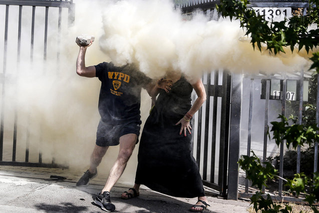 """Neighbours of the Chilean President Sebastian Pinera are sprayed with a fire extinguisher by protesters near Pinera's house in Santiago on Decembrer 1, 2019. Demonstrations on Sunday concentrated on calling for an """"unhappy birthday"""" to President Sebastian Pinera, on his 70th birthday. Near his home, in an affluent neighborhood of Santiago, dozens of protesters showed their rejection against the right-winger in front of a large security operation preventing the approach to Pinera's residence. (Photo by Javier Torres/AFP Photo)"""