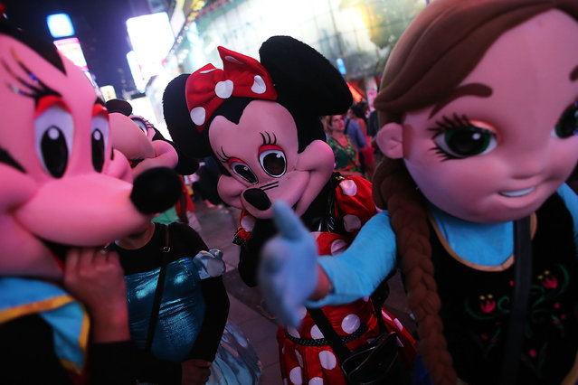 Street performers in costumes take a break in Times Square on August 19, 2015 in New York City. (Photo by Spencer Platt/Getty Images)