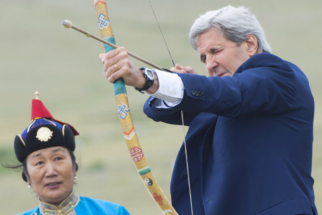 U.S. Secretary of State John Kerry shoots a bow and arrow as he participates in a Naadam ceremony, a competition which traditionally includes horse racing, Mongolian wrestling and archery, in Ulan Bator, Mongolia, June 5, 2016. (Photo by Saul Loeb/Reuters)