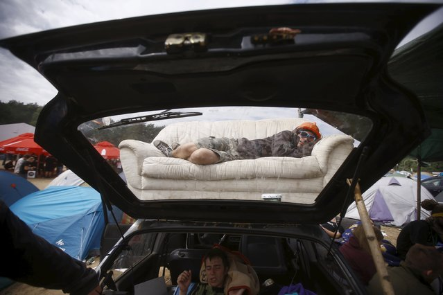 A man sleeps on a coach placed on the roof of a car during the 21st Woodstock Festival in Kostrzyn-upon-Odra, Poland July 31, 2015. (Photo by Kacper Pempel/Reuters)