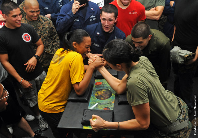 Seaman Denise Williams and Marine Sgt. Amanda Joseph, participate in an arm wrestling competition aboard the amphibious assault ship USS Makin Island (LHD 8)