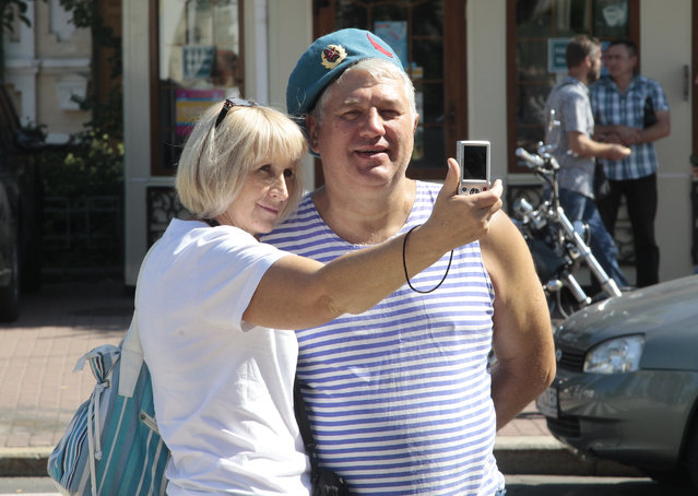 A woman takes a selfie photo with a paratrooper veteran to mark Paratrooper Day in Kiev, Ukraine, August 2, 2015. (Photo by Efrem Lukatsky/AP Photo)