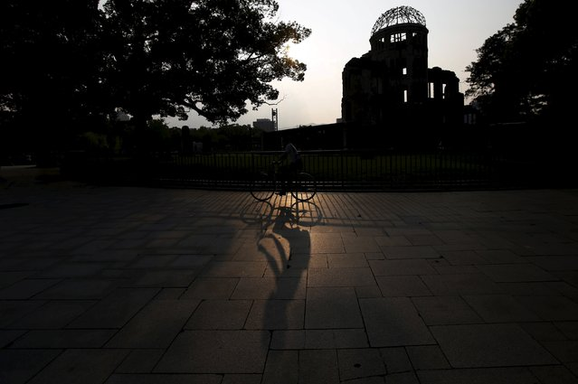 A Hiroshima resident riding a bicycle casts a shadow on the ground as he cycles past the Atomic Bomb Dome in Hiroshima, western Japan July 29, 2015. (Photo by Issei Kato/Reuters)