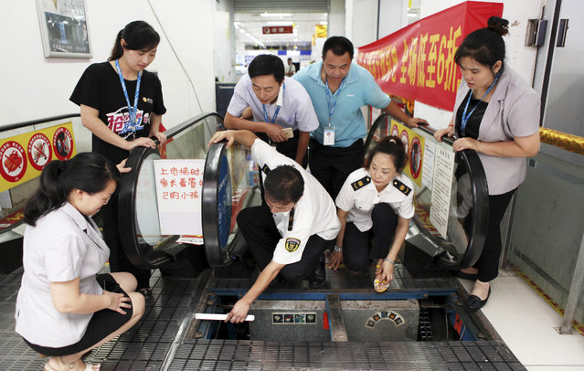 Staff members at an appliance store watch as officials from the local bureau of Quality and Technical Supervision inspect an escalator in Yongchuan district in southwest China's Chongqing Municipality Thursday July 30, 2015. The recent escalator accident that killed a woman in the central China city of Jingzhou has raised the public's awareness of escalator safety. (Photo by Color China Photo via AP Photo)