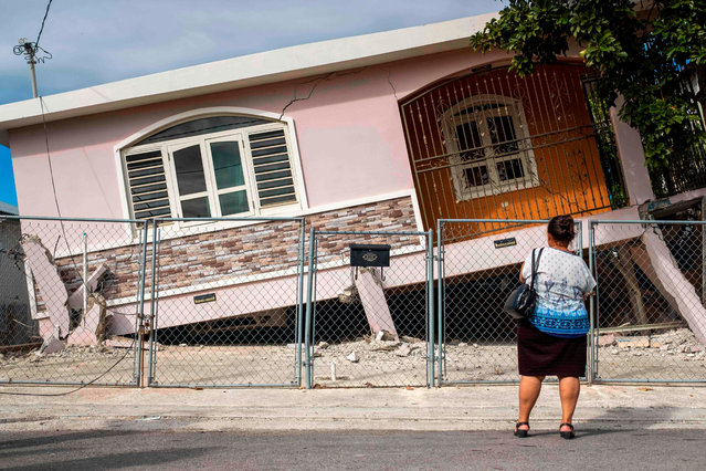 A woman stands in front of a house damaged by a 5.8 earthquake in Guanica, Puerto Rico on January 6, 2020.  A 5.8-magnitude earthquake shook Puerto Rico on January 6, 2020, toppling some structures and causing power outages and small landslides but there were no reports of casualties, the US Geological Survey said. The quake, just off the US territory's southern Caribbean coastline, was felt throughout much of the island, including the capital San Juan. Some 250,000 customers were hit by electric power outages after the quake, which struck at 6:32 am local time (1032GMT). (Photo by Ricardo Arduengo/AFP Photo)