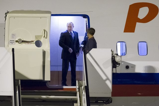 Russian President Vladimir Putin stands inside a plane upon arrival for the G-20 summit in Hamburg, northern Germany, Friday, July 7, 2017. After weeks of anticipation, President Donald Trump and Russian President Vladimir Putin will meet at an international summit in Germany. (Photo by Alexander Zemlianichenko/AP Photo)