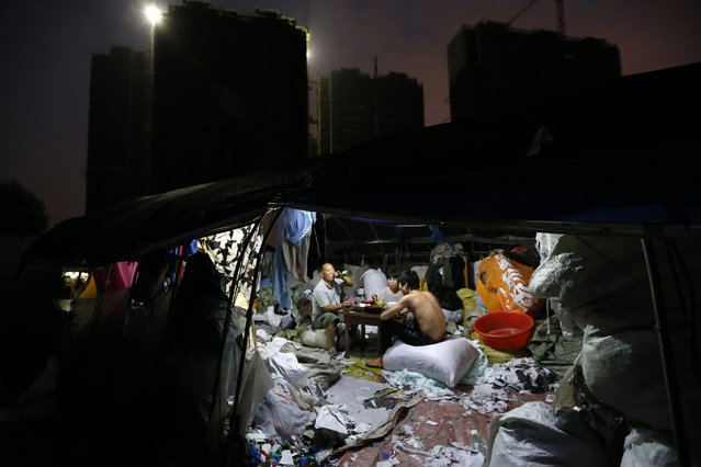 A migrant family have dinner at their makeshift shelters next to a construction site of new buildings in Zhejiang province, July 9, 2014. China's home prices eased further in June, two private surveys showed last Tuesday, adding to signs of a cooling housing market which is posing a growing risk to the broader economy. (Photo by William Hong/Reuters)