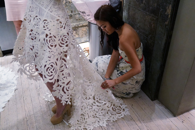 A designer is pictured backstage fixing a wedding dress made out of toilet paper before a fashion show in the Manhattan borough of New York City on July 20, 2017. (Photo by Carlo Allegri/Reuters)