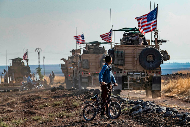 A Syrian boy on his bicycle looks at a convoy of US armoured vehicles patrolling fields near the northeastern town of Qahtaniyah at the border with Turkey, on October 31, 2019. US forces accompanied by Kurdish fighters of the Syrian Democratic Forces (SDF) patrolled part of Syria's border with Turkey, in the first such move since Washington withdrew troops from the area earlier this month, an AFP correspondent reported. (Photo by Delil Souleiman/AFP Photo)