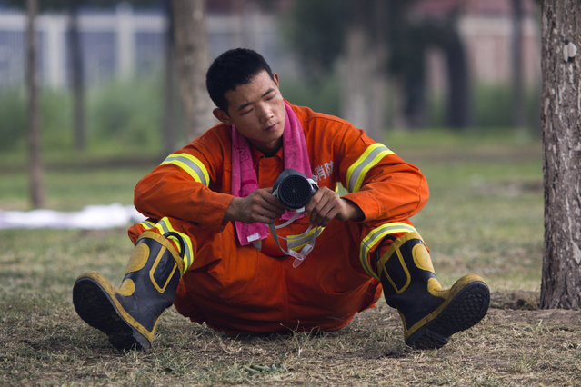 A Chinese firefighter adjusts his mask as he waits to be activated near the site of an explosion in northeastern China's Tianjin municipality Saturday, August 15, 2015. (Photo by Ng Han Guan/AP Photo)