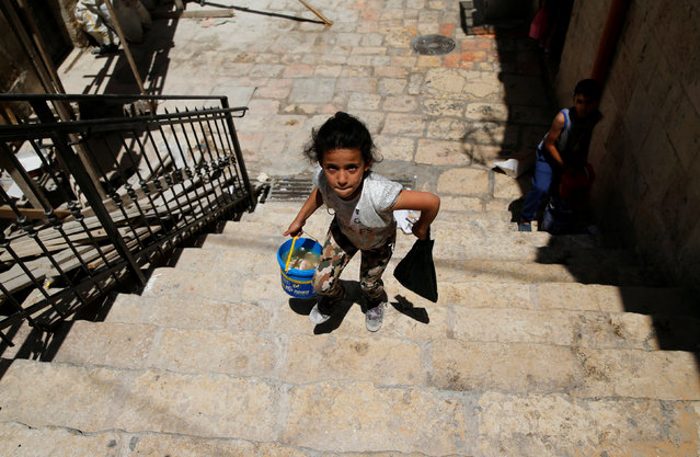 A Palestinian girl walks after she received a pack of food in the Old City of Jerusalem during the Muslim holy month of Ramadan June 22, 2016. (Photo by Ammar Awad/Reuters)