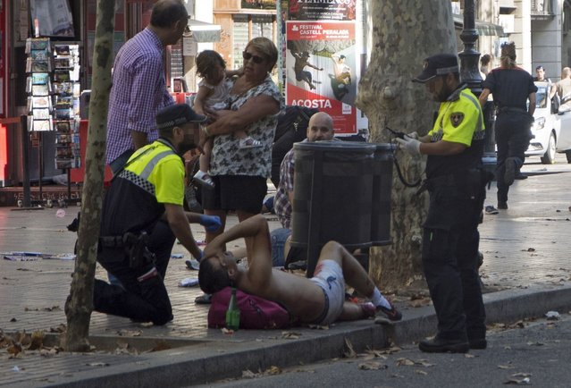 Mossos d'Esquadra Police officers attend injured people after a van crashed into pedestrians in Las Ramblas, downtown Barcelona, Spain, 17 August 2017. (Photo by David Armengou/EPA/Rex Features/Shutterstock)