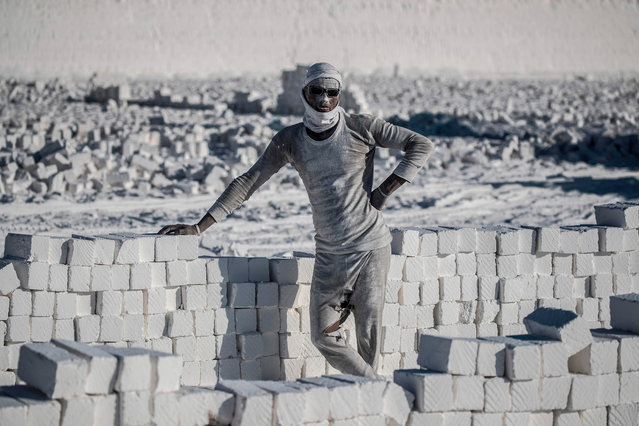 """A labourer poses for a picture at the """"White Mountain"""" limestone extraction quarry site near Egypt's southern city of Minya, some 265 kilometres south of the capital, on December 7, 2019. Covered in fine white dust, labourers at a limestone quarry in southern Egypt toil in brutal conditions with little workplace safety for paltry pay. Labourers work in shifts at the quarry in the so-called White Mountain east of the river Nile outside Minya, about 265 km south of the capital Cairo. (Photo by Khaled Desouki/AFP Photo)"""