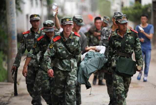 Paramilitary policemen carry an injured resident on a stretcher after an earthquake hit Ludian county of Zhaotong, Yunnan province August 3, 2014. A magnitude 6.5 earthquake struck southwestern China on Sunday, killing at least 150 people in a remote mountainous area of Yunnan province, causing some buildings, including a school, to collapse, Xinhua News Agency reported. (Photo by Reuters/China Daily)