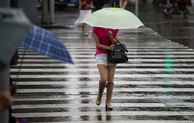 A woman holds an umbrella in the streets of Shanghai during rainfall on August 1, 2014. Chinese economic growth accelerated to a higher-than-expected 7.5 percent in the second quarter, up from 7.4 percent in the previous three months, which was the worst since a similar 7.4 percent expansion in July-September 2012. (Photo by Johannes Eisele/AFP Photo)